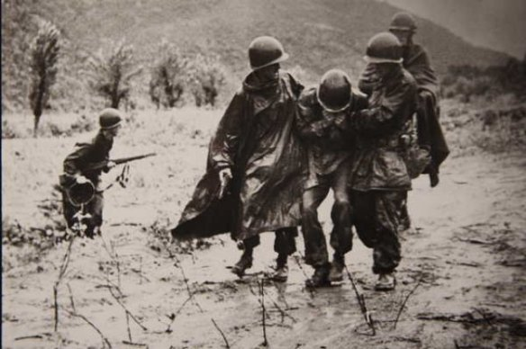 Chaplain Kapaun assists medical personnel with evacuation of a Soldier.