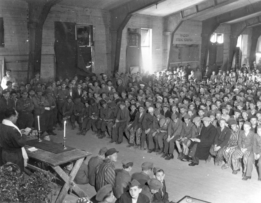 Chaplain Rabbi Hershel Schaecter conducts religious service for Buchenwald survivors. Click to enlarge.